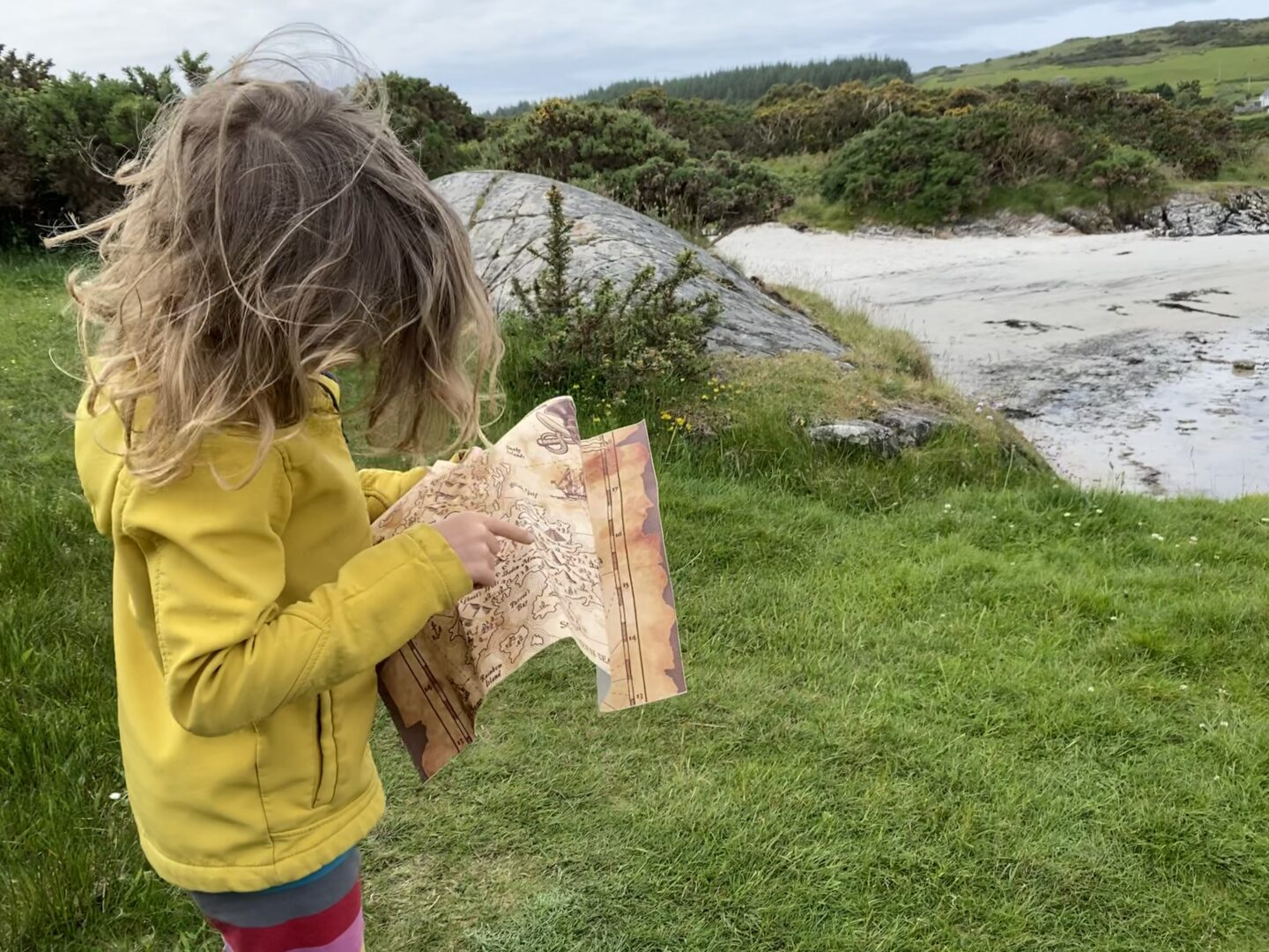 child looking at a pirate map at the beach