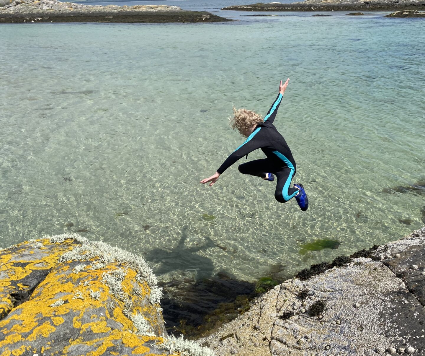 child jumping into water in Scotland