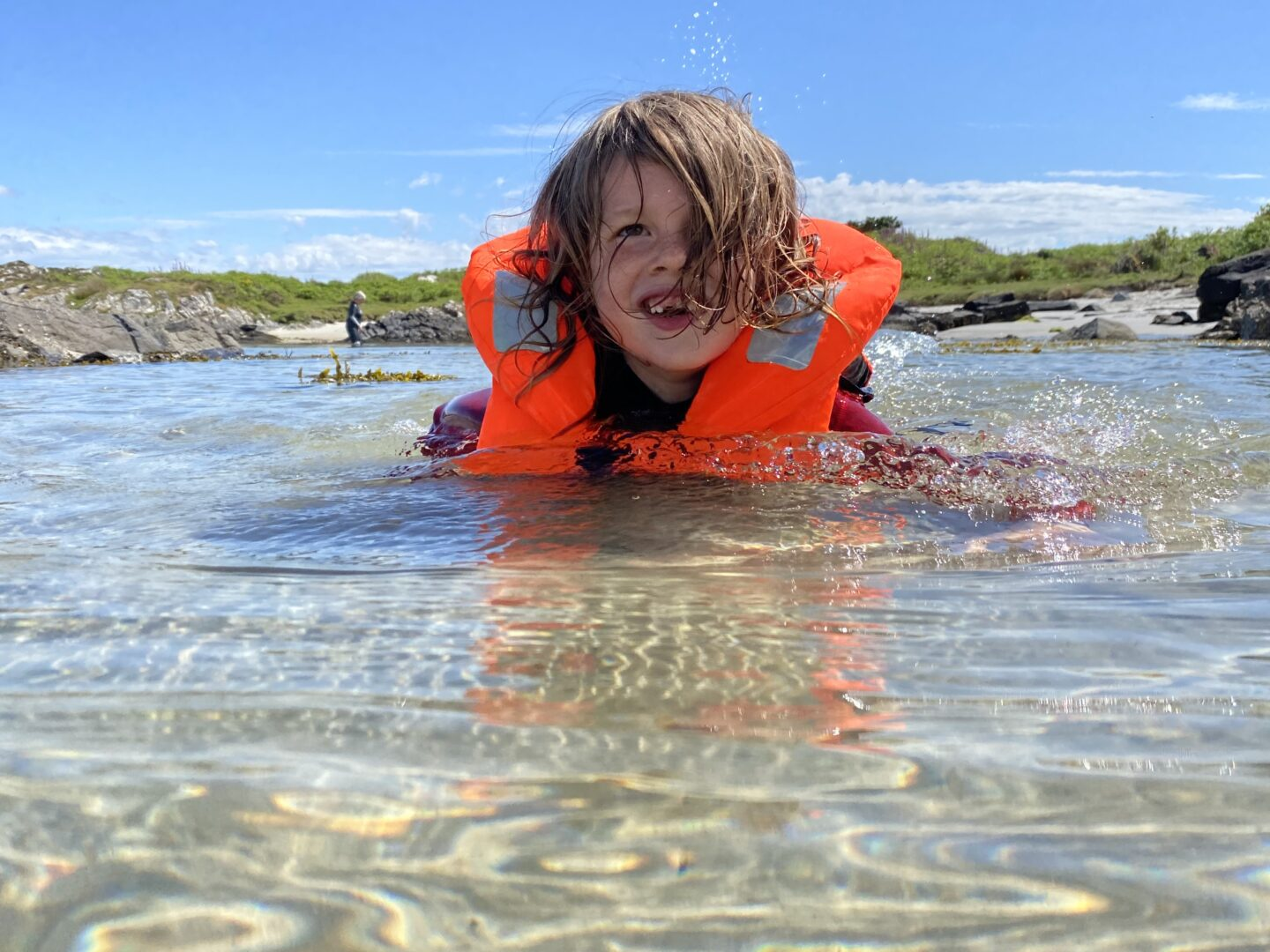 child swimming in the sea off Gigha with a buoyancy aid on