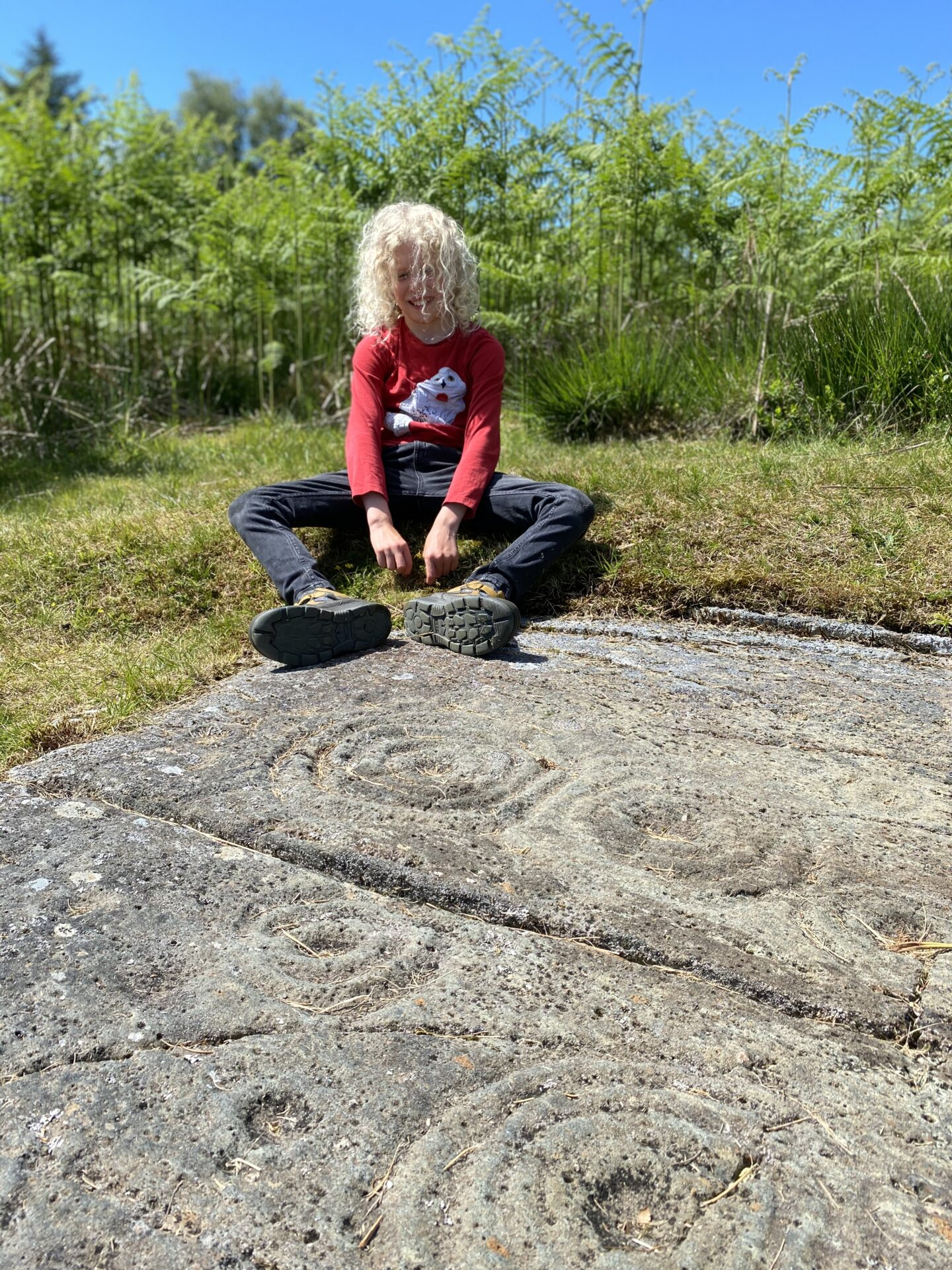 child sitting at the top of a slab of rock art near Crinan Scotland