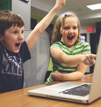 children cheering and pointing at a laptop