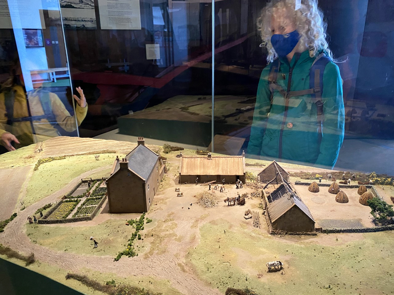 child looking at a model farm in museum