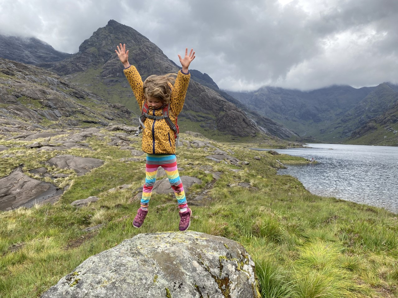 child jumping on rock beside Loch Coruisk with cuillin mountains behind shrouded in mist